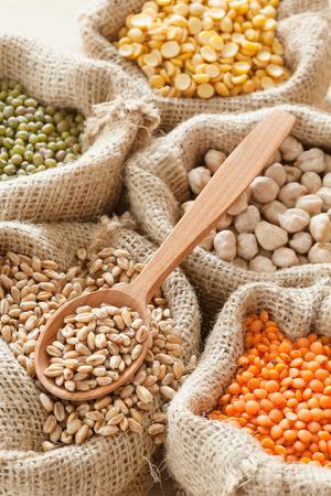 hessischen Beutel mit Weizen, Erbsen, Kichererbsen, rote Linsen und grüne Mungo, Holzlöffel Lizenzfreie Bilder