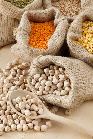 hessian bag with chickpeas and wooden spoon closeup; peas, wheat, red lentils and green mung on background photo