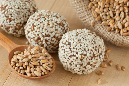 macrobiotic: macrobiotic healthy food. balls from ground wheat sprouts with sesame seeds and sack with seeds on kitchen table