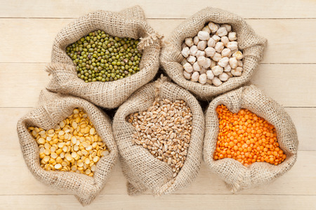 hessian bags with cereal grains: red lentils, peas, chick peas, wheat and green mung on wooden table, top view photo