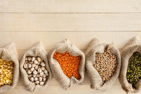 garbanzos: bolsas de arpillera con los granos de cereales: guisantes, garbanzos, lentejas rojas, trigo y mung verde en la mesa de madera Foto de archivo