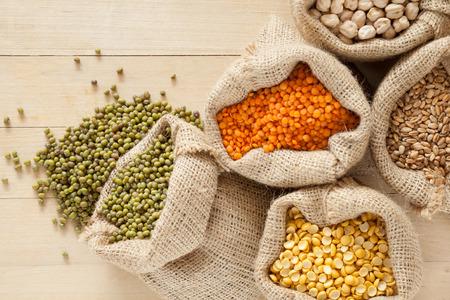 빨간색 렌즈 콩, 완두콩, 병아리 콩, 밀, 나무 테이블에 녹색 녹두 : 곡물과 가방