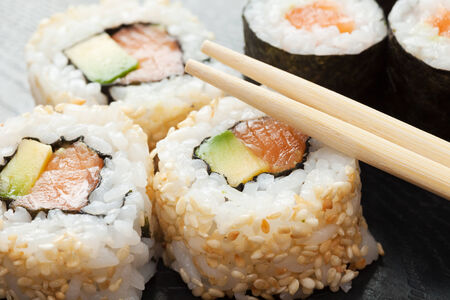 maki: sushi rolls on black wooden plate and chopsticks Stock Photo