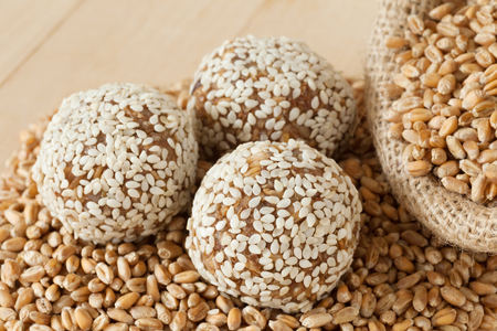 mingle: sweet balls from ground wheat sprouts with sesame seeds, grains in sack on wooden kitchen table Stock Photo