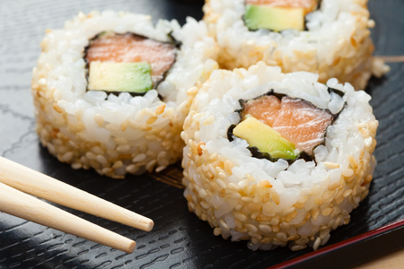 sushi rolls on black wooden plate and chopsticks photo