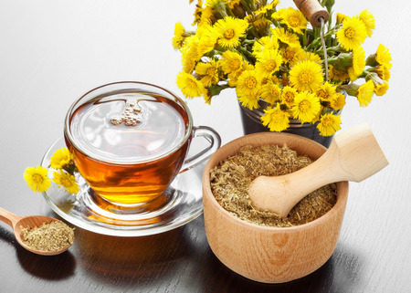 healthy tea in glass mug, bucket with coltsfoot flowers and mortar on table, herbal medicine photo