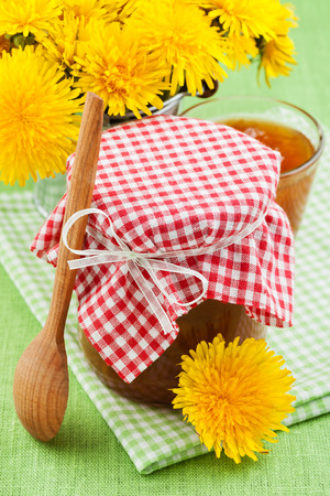 jar of dandelion jam and blowball flowers on table photo