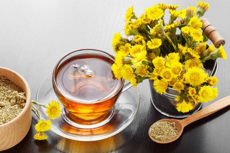 healthy tea in glass cup closeup, bucket with coltsfoot flowers and mortar on table, herbal medicine photo