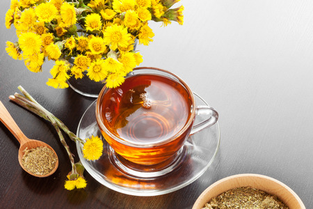 healthy tea closeup, bucket with coltsfoot flowers and mortar on dark table, herbal medicine photo