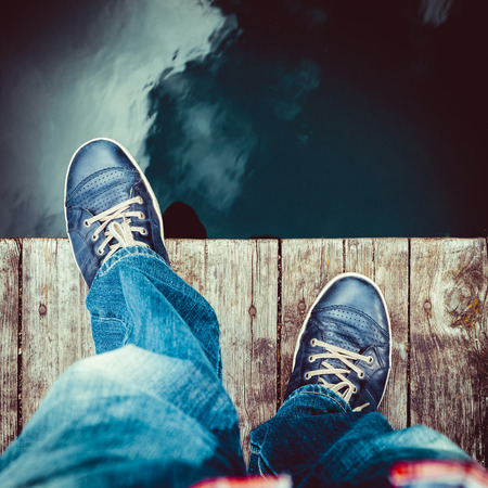 foot step: man on the pier takes a step into the water, from above