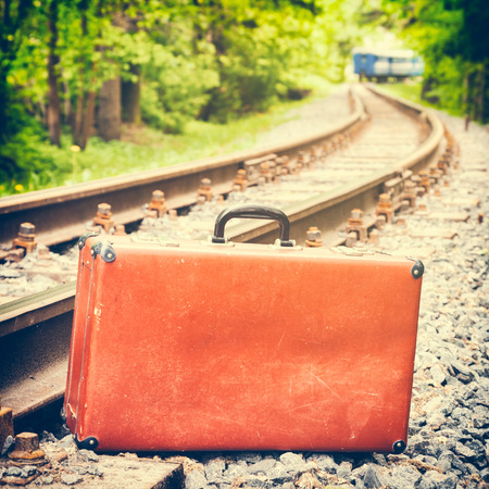 emigration: retro suitcase on the railway, train is off