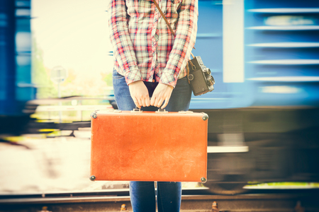 young woman with retro suitcase and camera on railway platform, train wagons on background Stock Photo