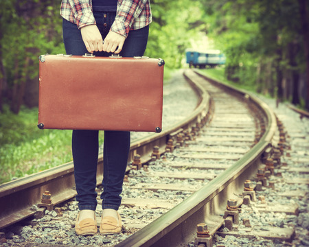 baggage train: young woman with old suitcase on railway, departing train on background, retro stylized