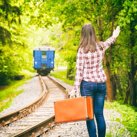 mujer joven con la maleta vieja agitando la mano, con salida del tren en el fondo Foto de archivo