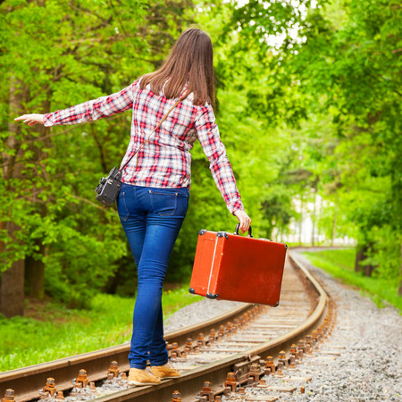 single track: girl with retro brown suitcase walking on the railway