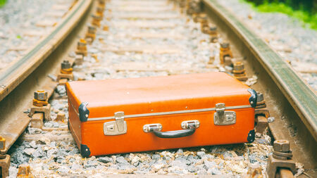 emigration:  brown vintage suitcase lying on the railway