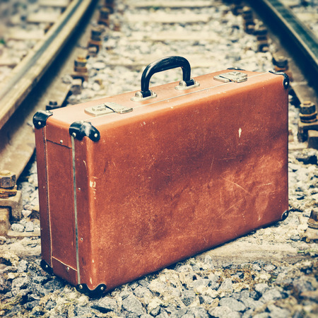 emigration: vintage brown suitcase standing on the railway