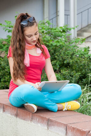 teen girl using a tablet pc sitting outdoors photo