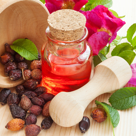 essential oil in glass bottle, dried rose-hip berries in wooden mortar and rose hip flowers on table Stock Photo
