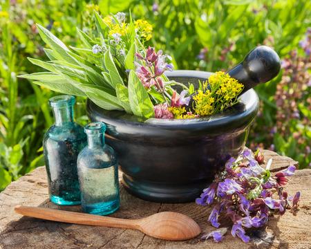 Mörtel mit heilenden Kräutern und Salbei, Glas Flasche ätherisches Öl im Freien