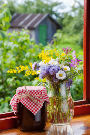 bunch of garden flowers and jam on windowsill photo