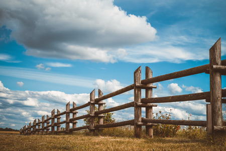 wood lawn: wooden rustic fence in village and blue sky with clouds Stock Photo