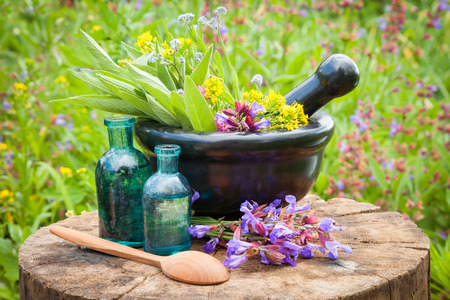 essential oil: black mortar with healing herbs and sage, glass bottle of essential oil outdoors
