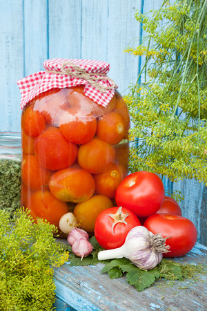 sterilized: Homemade pickled tomatoes in glass jar. Fresh vegetables, dill and garlic on wooden board