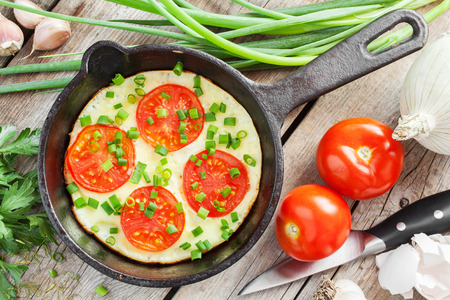 omelet: iron frying pan with scrambled eggs and tomatoes on wooden rustic table Stock Photo