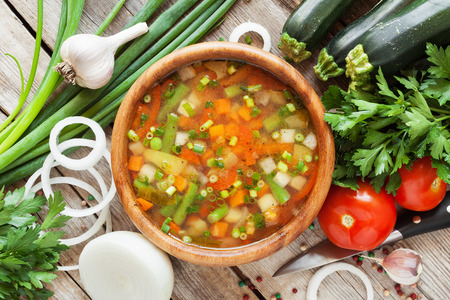 vegetable soup in wooden bowl and ingredients on wooden rustic table. top view photo