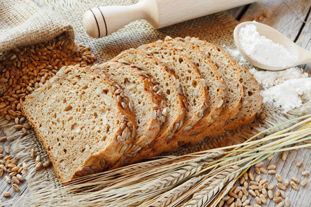 groat: bread slices and rye ears on table Stock Photo