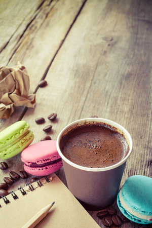 macaroons, espresso coffee cup and sketch book on wooden rustic table, vintage stylized photo