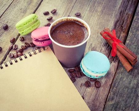 macaroons, espresso coffee cup, cinnamon sticks and sketch book on wooden rustic table, vintage stylized photo photo