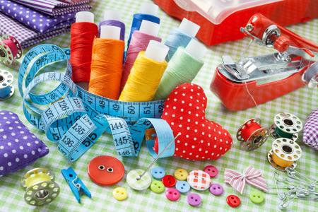 kit de costura: Artículos a medida: carretes de hilo de colores, botones, telas, cinta métrica, alfiletero, pequeña máquina de coser y cinta métrica