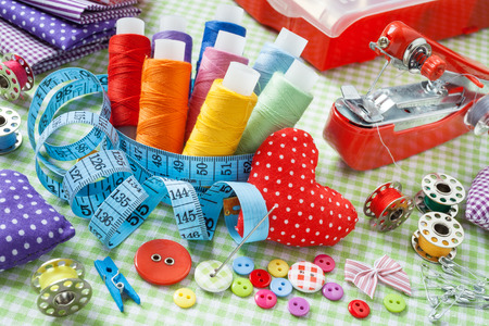 Tailor items: spools of colorful thread, buttons, fabrics, measuring tape, pincushion, small sewing machine and measuring tape photo