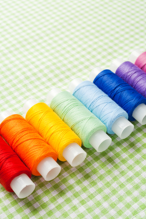 row of thread spools in rainbow colors photo