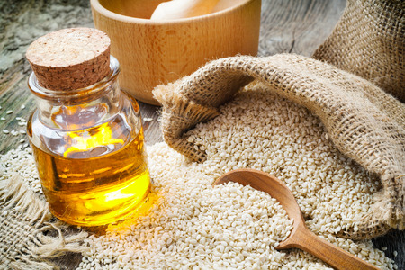 gunny bag: sesame seeds in sack and bottle of oil on wooden rustic table