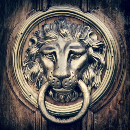 Door knocker, handle - lion head. Vintage stylized photo.