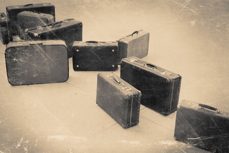 emigration: group of vintage suitcase on tiled floor, retro stylized in black and white color photo Stock Photo