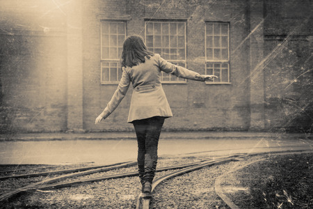 balance beam: girl walking on the railway, retro stylized in black and white colors photo Stock Photo