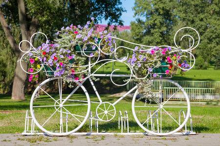 decorated bike: Bicicletta portando fiori decorativi vintage all'aperto Archivio Fotografico