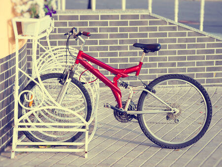 rack wheel: Lonely red bicycle on a parking Stock Photo