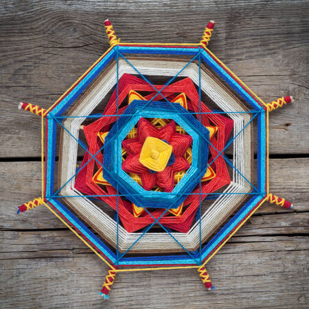 Knitted tibetan mandala from threads on old wooden plank, top view photo