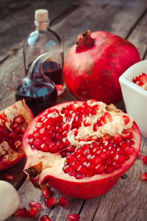 Pomegranate and bottles of essence or tincture on wooden table