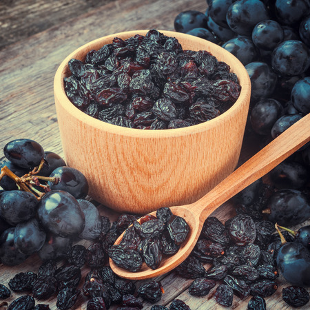 raisins in bowl and blue grapes on old rustic table Stock Photo