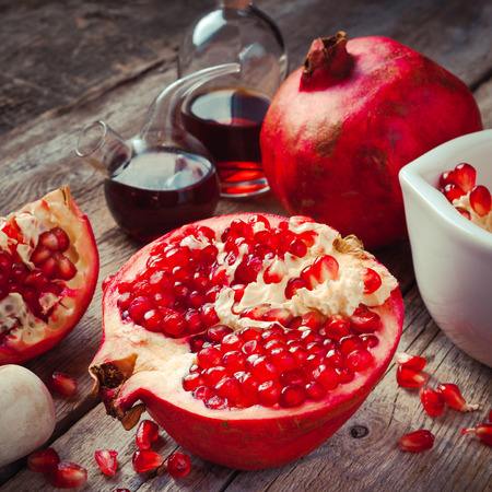 Pomegranate and bottles of essence or tincture on wooden rustic table Imagens