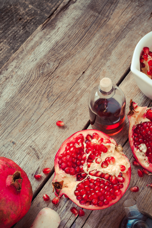 essence: Pomegranate and bottles of essence or tincture on wooden rustic table, top view Stock Photo