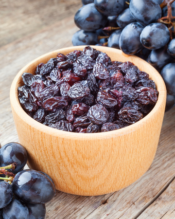 raisins: raisins in bowl and blue grapes on old wooden rustic table Stock Photo
