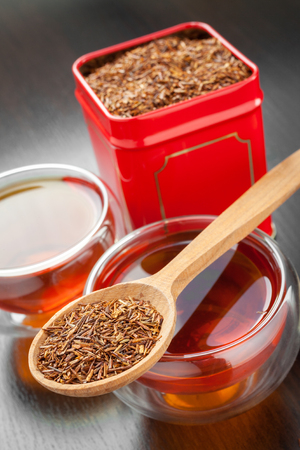 rooibos in wooden spoon, two tea cups and tea tin box on table photo