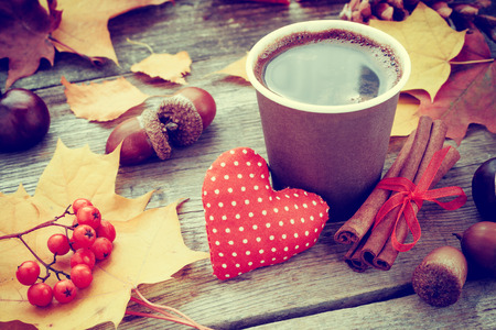heart heat: warming coffee cup, red heart and autumn still life on old table Stock Photo